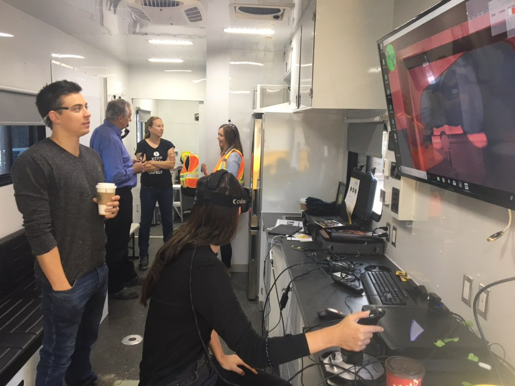 Members of the public exploring the inside of the mobile research lab (M-CROSH), including trying a virtual reality mining simulator, with Brandon Vance and Dr Sandra Dorman as guides