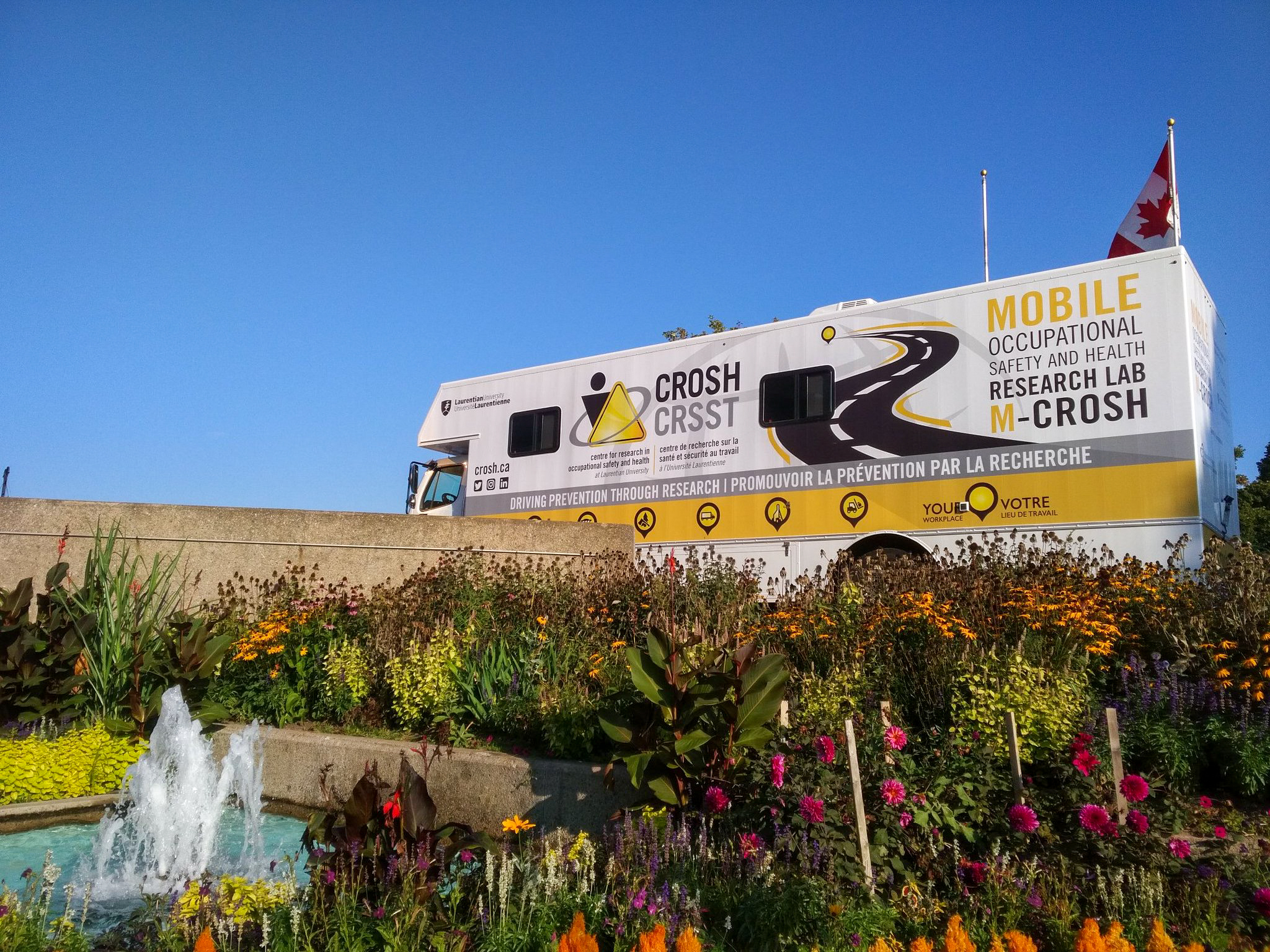 The mobile research lab (M-CROSH) parked next to a garden