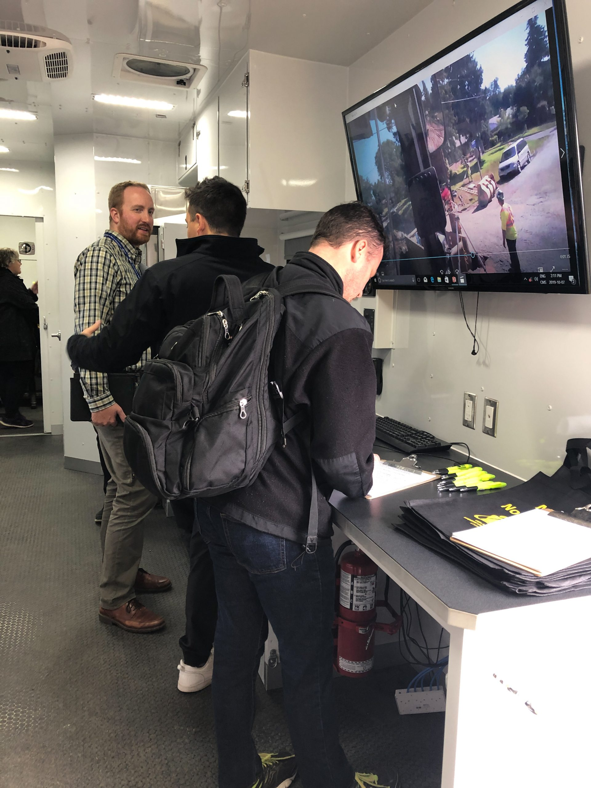 Visitors exploring the inside of the CROSH mobile research lab while a video plays on a monitor