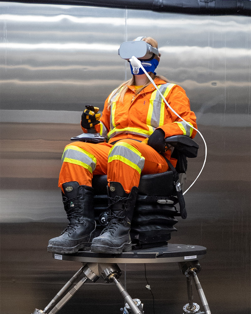 Person sitting on robotic motion platform (rotopod) wearing full personal protective equipment, a virtual reality headset, with a hose going into their mouth to measure gas exchange